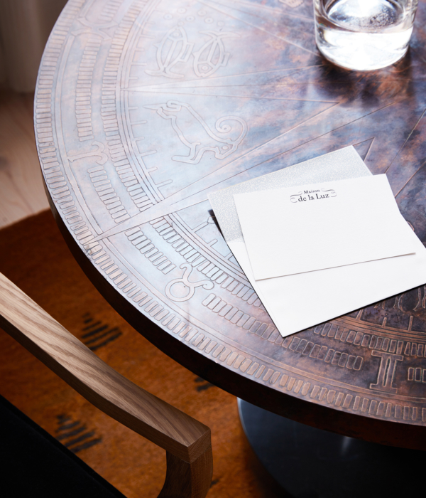 Coffee table with astrological engravings and hotel stationary in luxury hotel room at Maison de la Luz in New Orleans